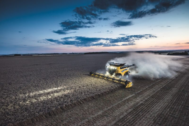 New Holland combine harvesting wheat field